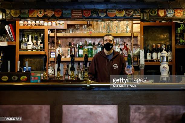 Paul Silcock, landlord and co-owner of The Gardeners Arms public house, poses for a photograph behind the bar, in Oxford on January 29, 2021. - The...