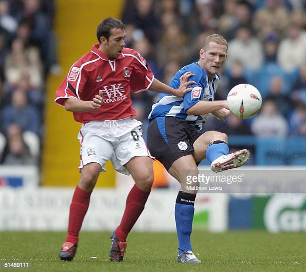 Paul Smith of Sheffield clears the ball away from Michael Chopra of Barnsley during the CocaCola Division One match between Sheffield Wednesday and...