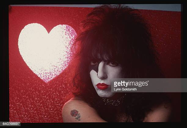 Paul Stanley is shown in full makeup against a red background with a white heart in it in this studio portrait Undated