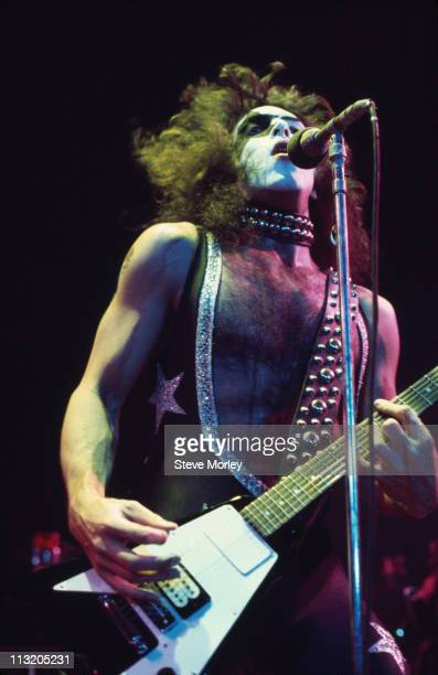 Paul Stanley US rock guitarist and singer with rock band Kiss playing the guitar and singing into a mirophone during a live concert performance by...