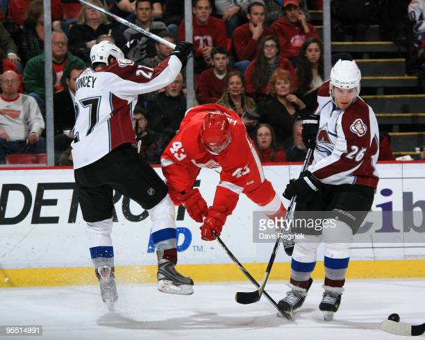 Paul Stastny of the Colorado Avalanche and teammate Kyle Quincey look for the loose puck as Darren Helm of the Detroit Red Wings flys through midair...