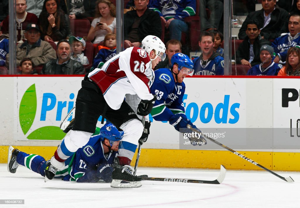 Paul Stastny #26 of the Colorado Avalanche appears to have the upper hand on Henrik Sedin #33 and Daniel Sedin #22 of the Vancouver Canucks during their NHL game at Rogers Arena January 30, 2013 in Vancouver, British Columbia, Canada. Vancouver won 3-0.