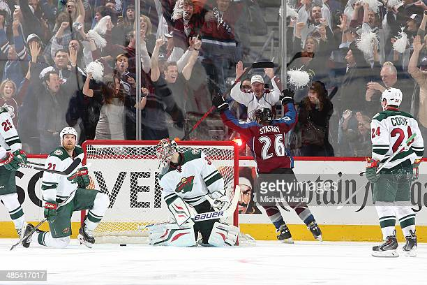 Paul Stastny of the Colorado Avalanche scores the game winning goal in overtime as members of the Minnesota Wild react in Game One of the First Round...