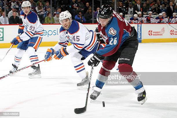 Paul Stastny of the Colorado Avalanche tries to control the puck against Mark Fistric and Ryan Smyth of the Edmonton Oilers at the Pepsi Center on...