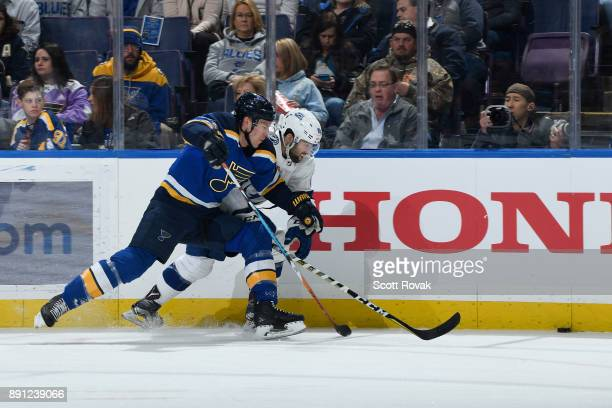 Paul Stastny of the St Louis Blues and Cory Conacher of the Tampa Bay Lightning battle for the puck at Scottrade Center on December 12 2017 in St...