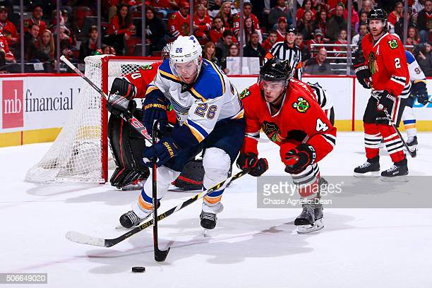 Paul Stastny of the St Louis Blues and Niklas Hjalmarsson of the Chicago Blackhawks chase the puck in the third period of the NHL game at the United...