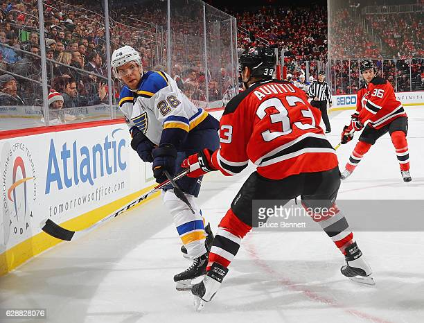 Paul Stastny of the St Louis Blues backhands the puck past Yohann Auvitu of the New Jersey Devils during the first periodof the St Louis Blues at the...