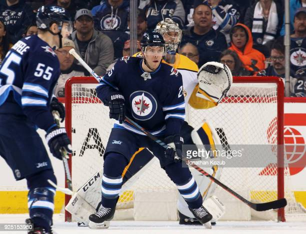 Paul Stastny of the Winnipeg Jets sets a screen in front of goaltender Pekka Rinne of the Nashville Predators as they keep an eye on the play during...