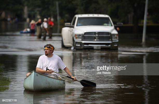 Paul steers his canoe as he looks to help people retrieve items out of homes that were inundated with water in an area where a mandatory evacuation...