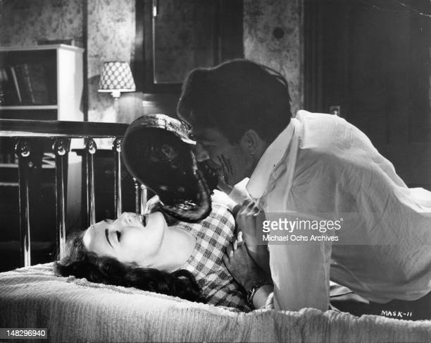 Paul Stevens as a psychiatrist tries to place a mask on Claudette Nevins in a scene from the film 'The Mask' 1961
