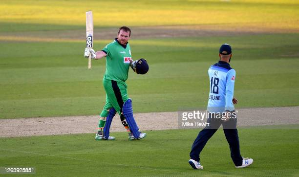 Paul Stirling of Ireland celebrates reaching his century watched on by Moeen Ali of England during the Third One Day International between England...