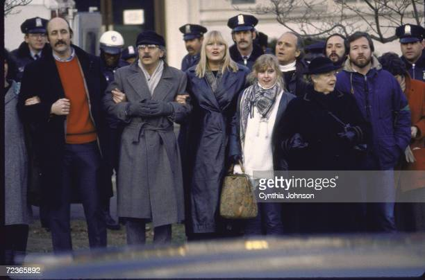 Paul Stookey Peter Yarrow and Mary Travers of folk group Peter Paul and Mary and others marching during antiapartheid demo