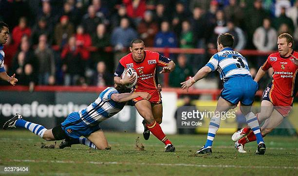 Paul Sykes of London Broncos gets tackled by Sean O'Loughlin and Martin Aspinwall of Wigan Warriors during the Super Rugby League match between the...