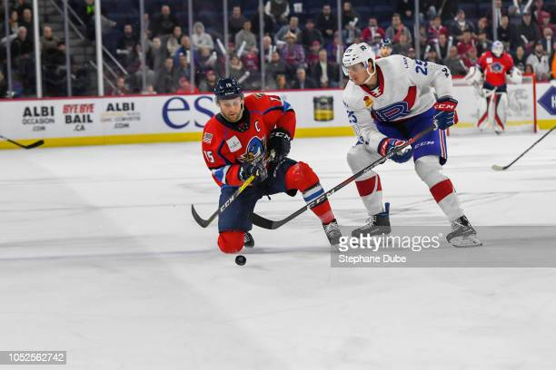 Paul Thompson of the Springfield Thunderbirds is on one knee trying to shoot the puck while Michael McCarron of the Laval Rocket is about to hit him...
