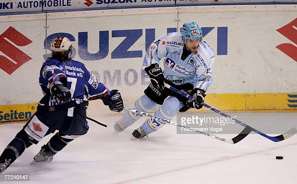 Paul Traynor of Iserlohn and Francois Fortier of Hamburg fight for the puck during the DEL match between Hamburg Freezers and Iserlohn Roosters at...