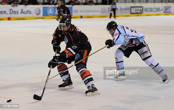 Paul Traynor of Wolfsburg is challenged byRene Roethke of Straubing during the DEL match between Grizzly Adams Wolfsburg and Straubing Tigers at the...