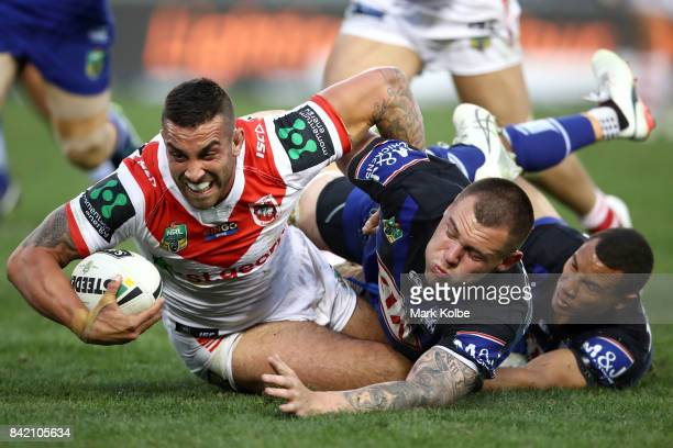 Paul Vaughan of the Dragons is tackled by David Klemmer and Moses Mbye of the Bulldogs during the round 26 NRL match between the St George Illawarra...