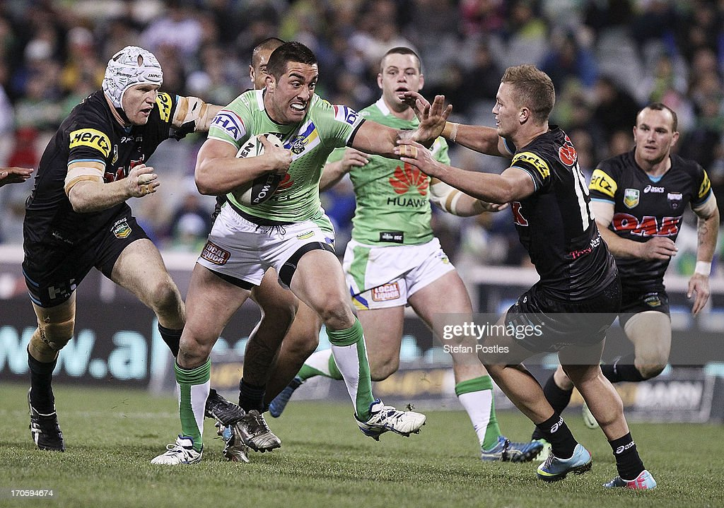 Paul Vaughan of the Raiders fends off a tackle during the round 14 NRL match between the Canberra Raiders and the Penrtih Panthers at Canberra Stadium on June 15, 2013 in Canberra, Australia.