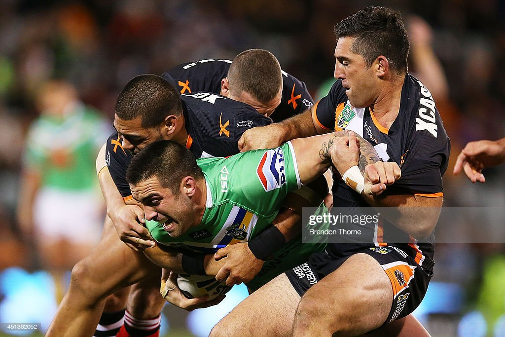 Paul Vaughan of the Raiders is tackled by is tackled by the Tigers defence during the round 16 NRL match between the Wests Tigers and the Canberra Raiders at Campbelltown Sports Stadium on June 28, 2014 in Sydney, Australia.