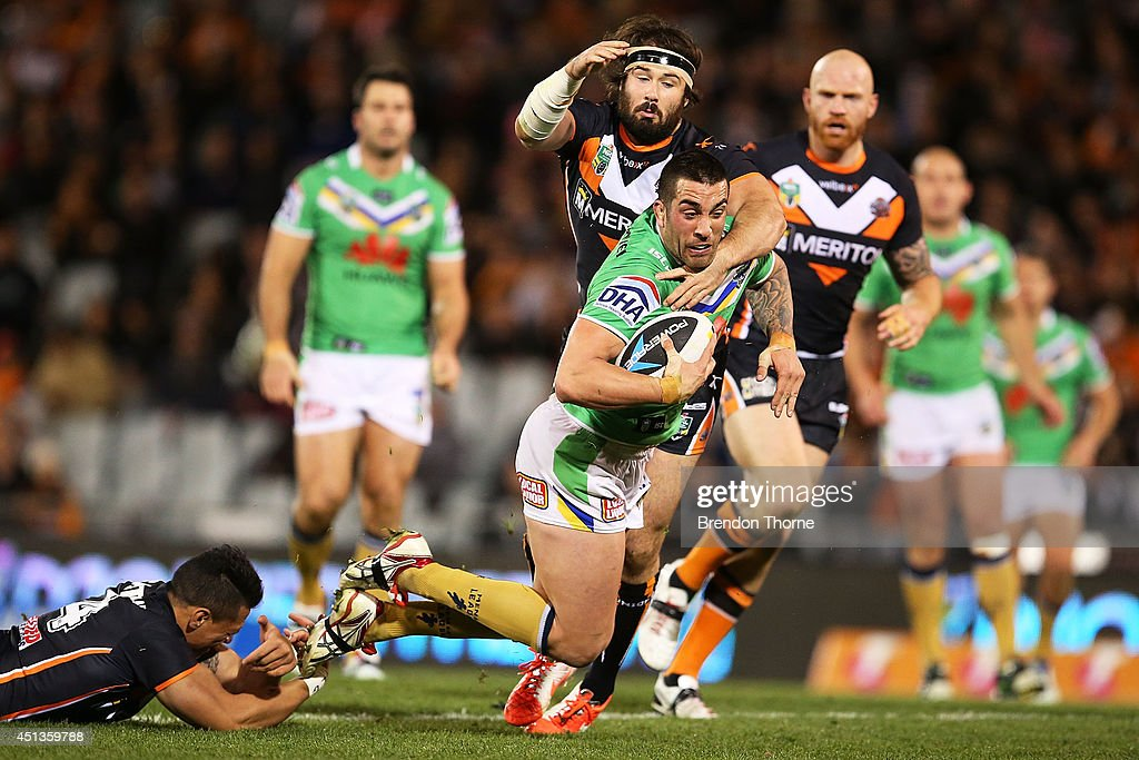 Paul Vaughan of the Raiders is tackled by Sauaso Sue and Aaron Woods of the Tigers during the round 16 NRL match between the Wests Tigers and the Canberra Raiders at Campbelltown Sports Stadium on June 28, 2014 in Sydney, Australia.