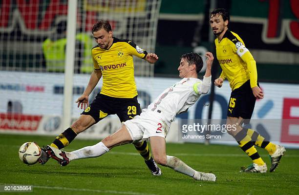 Paul Verhaegh of Augsburg and Marcel Schmelzer and Mats Hummels of Dortmund vie for the ball during the round of sixteen German Cup match between FC...