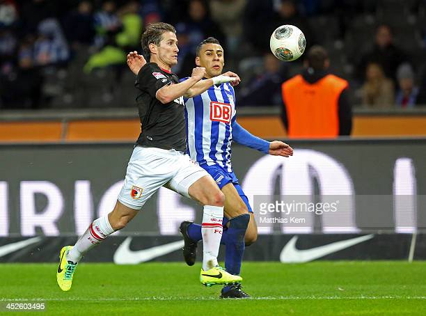 Paul Verhaegh of Augsburg battles for the ball with Aenis Ben Hatira of Berlin during the Bundesliga match between Hertha BSC and FC Augsburg at...