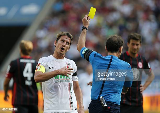 Paul Verhaegh of Augsburg is showing the yellow card by Referee Florian Meyer during the Bundesliga match between Eintracht Frankfurt and FC Augsburg...