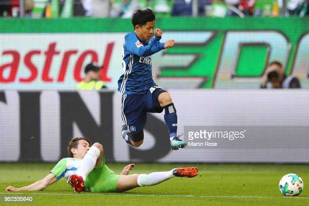 Paul Verhaegh of Wolfsburg tires to stop Tatsuya Ito of Hamburg during the Bundesliga match between VfL Wolfsburg and Hamburger SV at Volkswagen...