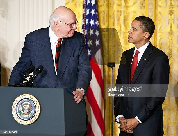 Paul Volcker former chairman of the Federal Reserve left looks toward to US President Barack Obama while speaking in the East Room of the White House...