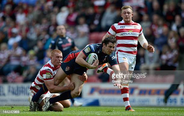 Paul Wellens of St Helens is tackled by Jack Hughes of Wigan during the Carnegie Challenge Cup Quarter Final match between Wigan and St Helens at the...