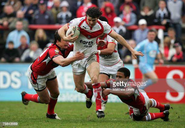 Paul Wellens of St.Helens breaks through the tackles of Stuart Littler and Jordan Turner of Salford during the engage Super League match between...