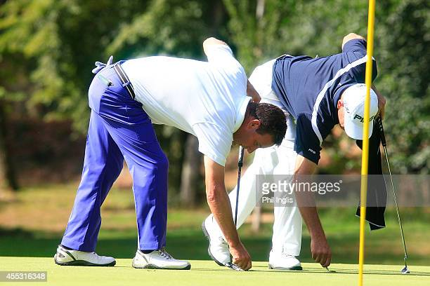 Paul Wesselingh of England iand Peter Fowler of Australia repair pitchmarks on the 3rd green during the first round of the Senior Open de Portugal...
