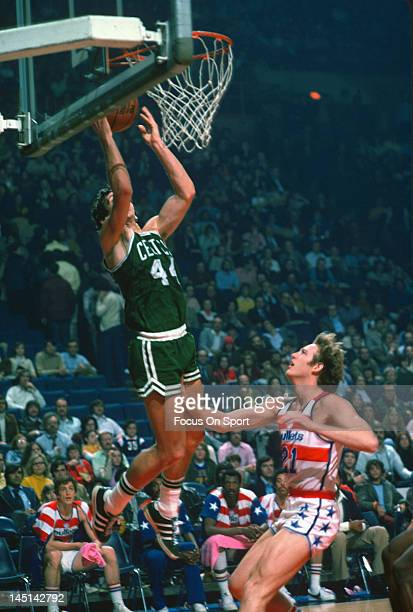 Paul Westphal of the Boston Celtics lays the ball up over Dick Gibbs of the Washington Bullets during an NBA basketball game circa 1975 at the...