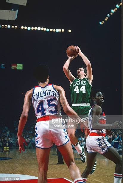 Paul Westphal of the Boston Celtics shoot over Kevin Porter and Phil Chenier of the Washington Bullets during an NBA basketball game circa 1975 at...