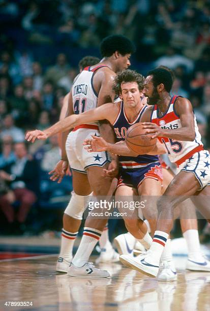 Paul Westphal of the Phoenix Suns fights through the pick of Wes Unseld to guard Charles Johnson of the Washington Bullets during an NBA basketball...