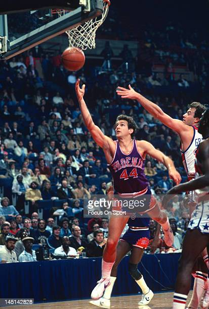 Paul Westphal of the Phoenix Suns lays the ball up over Kevin Grevey of the Washington Bullets during an NBA basketball game circa 1978 at the...
