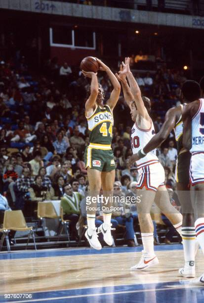 Paul Westphal of the Seattle Supersonics shoots over Ernie Grunfeld of the Kansas City Kings during an NBA basketball game circa 1980 at the Kemper...