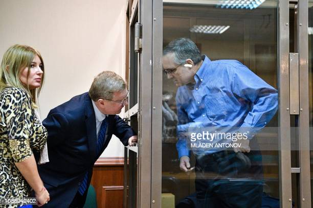 Paul Whelan a former US Marine accused of espionage and arrested in Russia speaks with his lawyers from inside a defendants' cage during a hearing at...