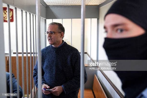 Paul Whelan a former US Marine accused of spying and arrested in Russia stands inside a defendants' cage during a hearing at a court in Moscow on...