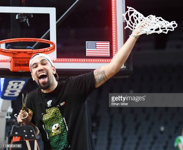 Paul White of the Oregon Ducks celebrates after cutting down a net following the team's 68-48 victory over the Washington Huskies to win the...