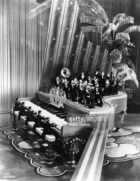 Paul Whiteman and his band on the giant grand piano set featured in the film 'King of Jazz', directed by John Murray Anderson for Universal Studios.