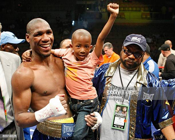 Paul Williams holds his son Paul Williams Jr as he and his trainer George Peterson celebrate defeating Winky Wright in a unanimous decision in their...