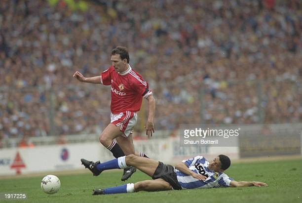 Paul Williams of Sheffield Wednesday tries to tackle Bryan Robson of Manchester United during the Rumbelows Cup final at Wembley Stadium in London...