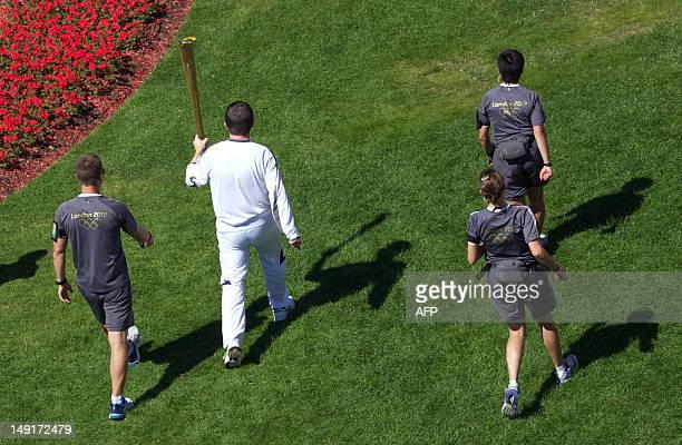 Paul Woodham walks past the Olympic rings while carrying the Olympic flame at Kew Gardens in Richmond London on July 24 2012 three days before the...