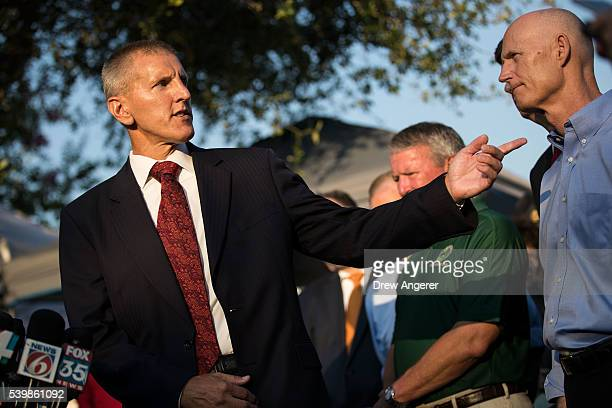 Paul Wysopal Federal Bureau of Investigation special agent in charge of the Tampa Division gestures toward Florida Governor Rick Scott as he speaks...