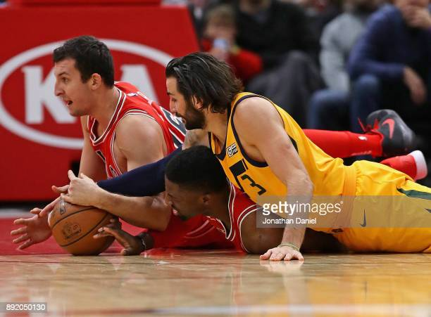 Paul Zipser and David Nwaba of the Chicago Bulls battle for a loose ball with Ricky Rubio of the Utah Jazz at the United Center on December 13 2017...