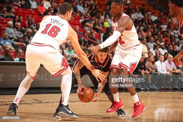 Paul Zipser and Kris Dunn of the Chicago Bulls cover Tyler Johnson of the Miami Heat during the game on November 1 2017 at American Airlines Arena in...