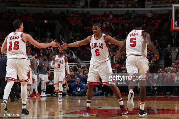 Paul Zipser Cristiano Felicio and Bobby Portis of the Chicago Bulls shake hands during the game against the Brooklyn Nets on April 12 2017 at the...