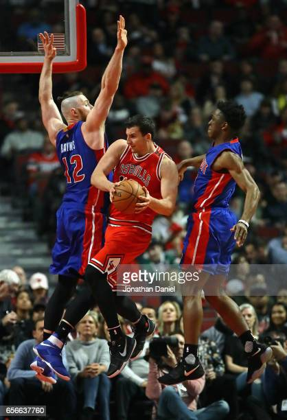 Paul Zipser of the Chicago Bulls leaps to pass between Aron Baynes and Stanley Johnson of the Detroit Pistons at the United Center on March 22, 2017...