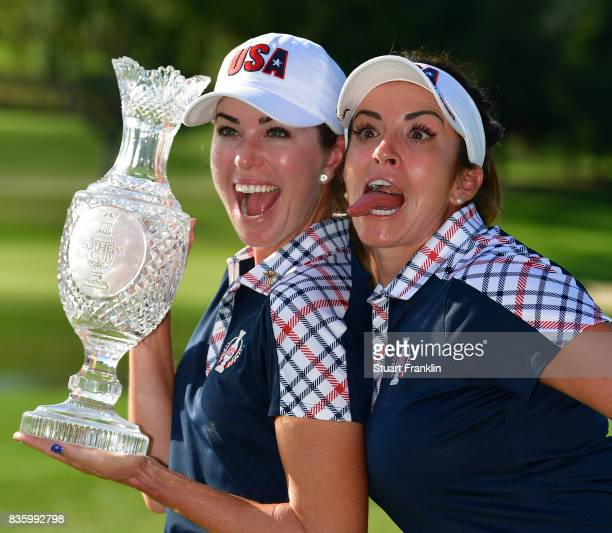 Paula Creamer and Gerina Piller of Team USA hold the Solheim Cup trophy after the final day singles matches of The Solheim Cup at Des Moines Golf and...